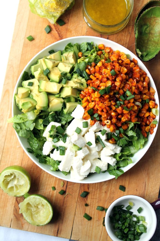 A plate of roasted corn salad with avocado and mozzarella