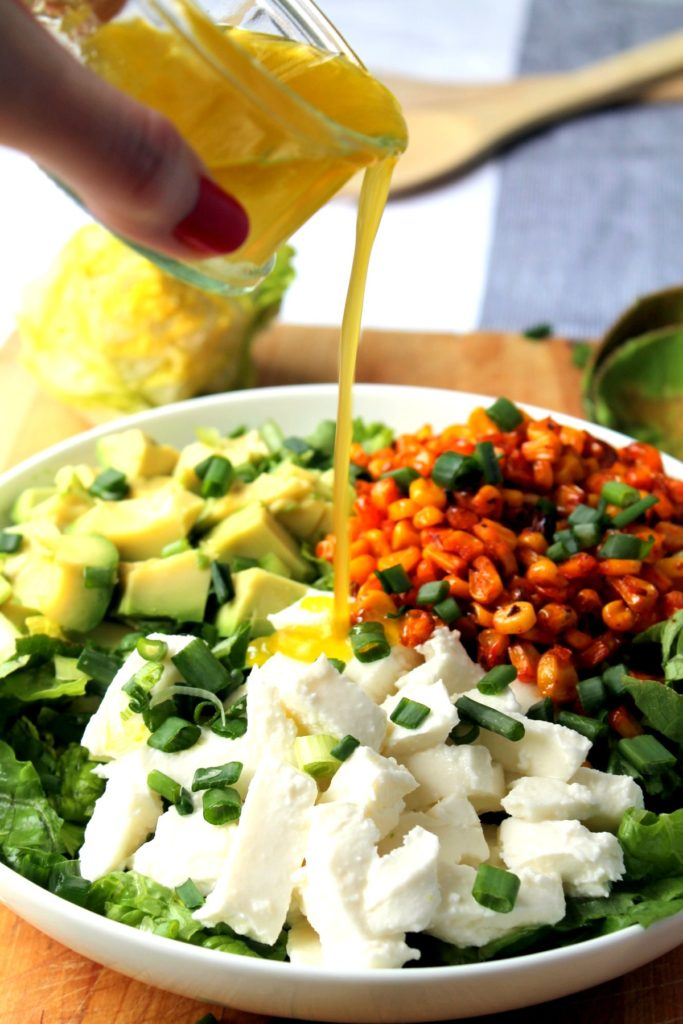 Honey lime salad dressing being poured onto the roasted corn salad