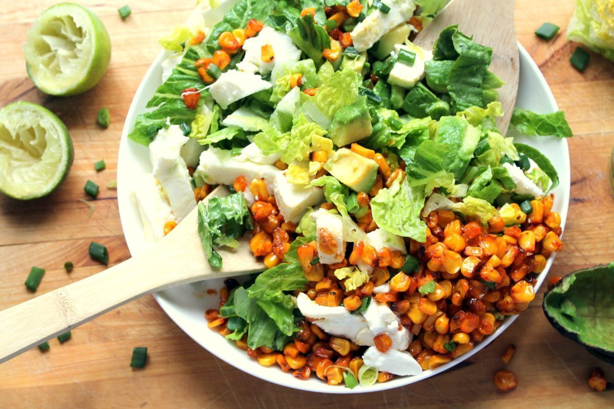 A plate of roasted corn salad garnished with limes