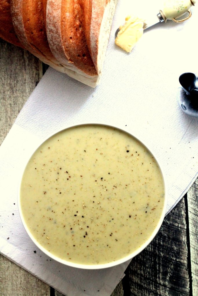 A top down view of of broccoli stilton soup with bread