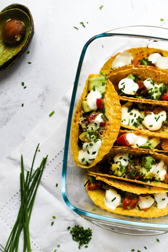 Oven baked bean and smoked cheese tacos with some garnishes.