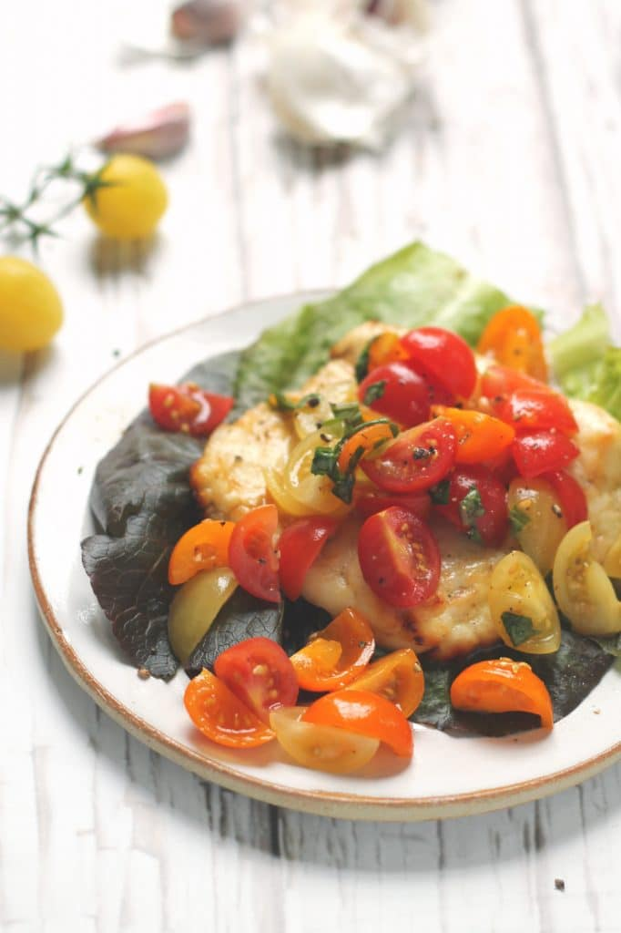 A straight on image of baked halloumi topped with cherry tomato bruschetta topping - atop a bed of lettuce leaves, with garlic and tomatoes in the background.