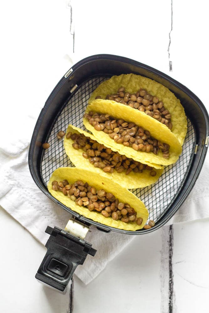 Tacos being prepared in an air fryer.